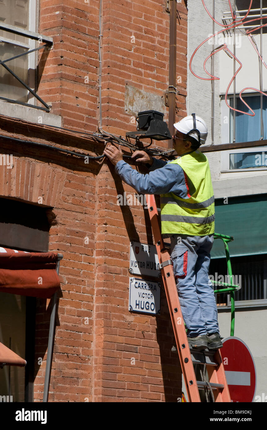 Electrician on top of a ladder performs a repair job in the center of Toulouse. - Stock Image