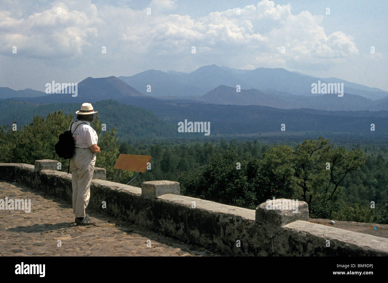 Tourist looking out over lava fields towards Volcan Paricutin volcano, Angahuan, Michoacan, Mexico - Stock Image