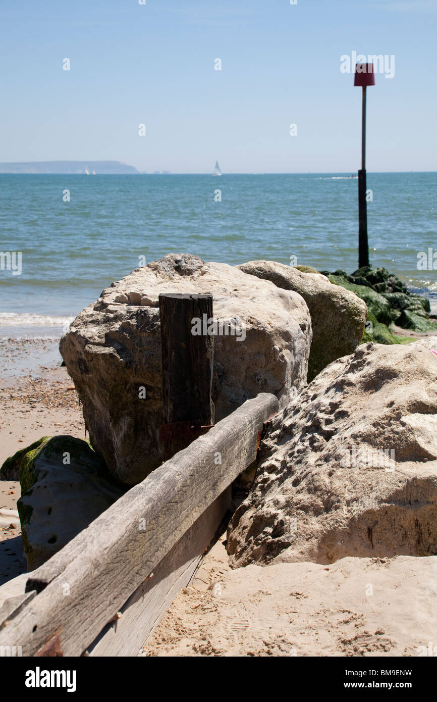 wooden and stone groyne with marker poll on beach at Mudeford - Stock Image
