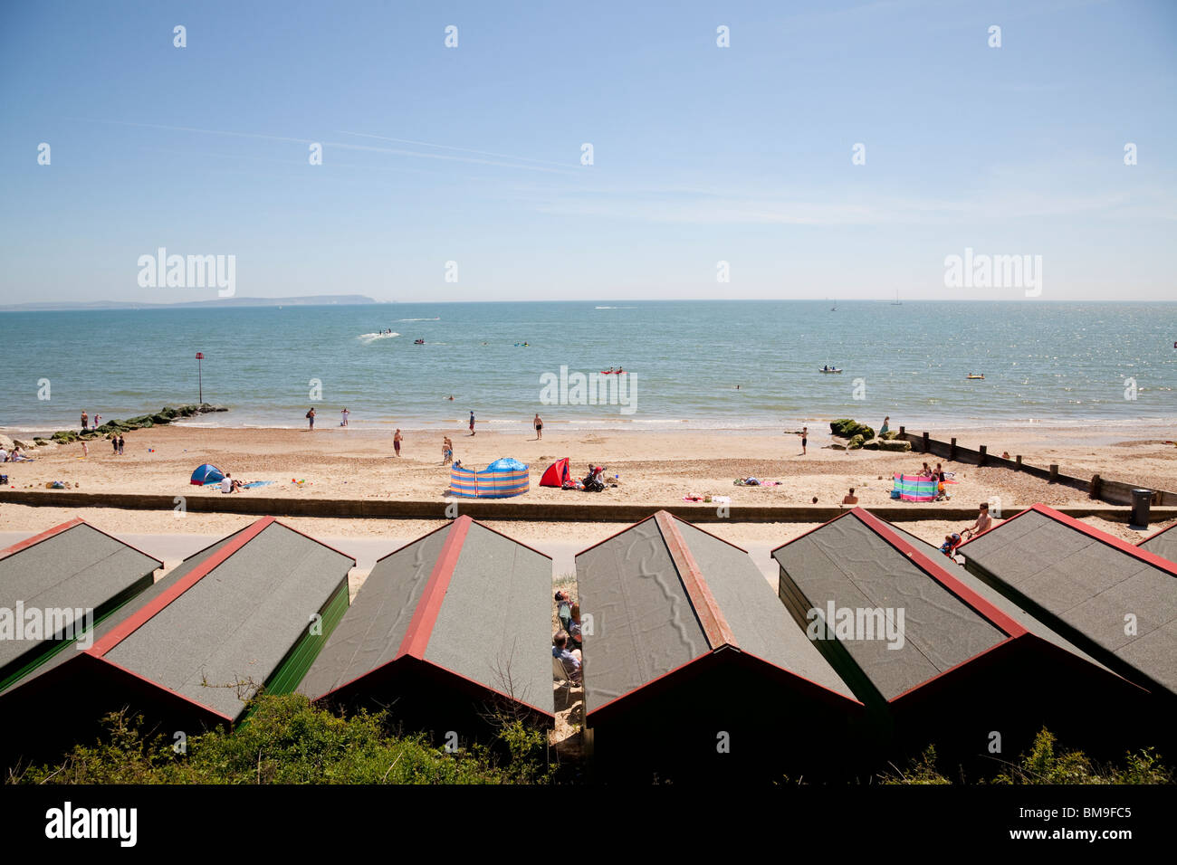 looking over beach hut roofs towards beach and sea at Mudeford - Stock Image