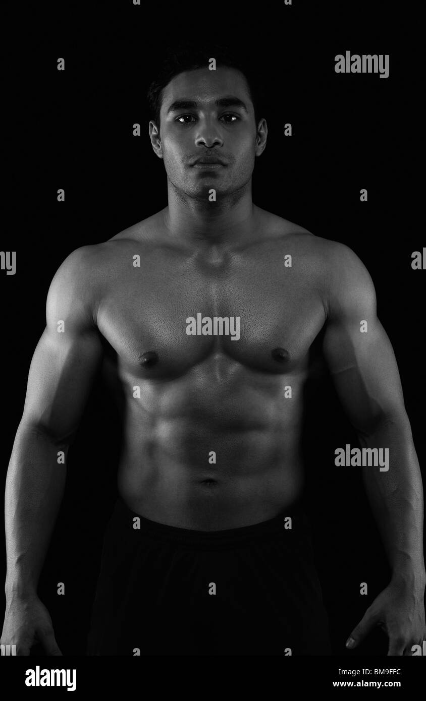 Portrait of a muscular man showing his abs - Stock Image