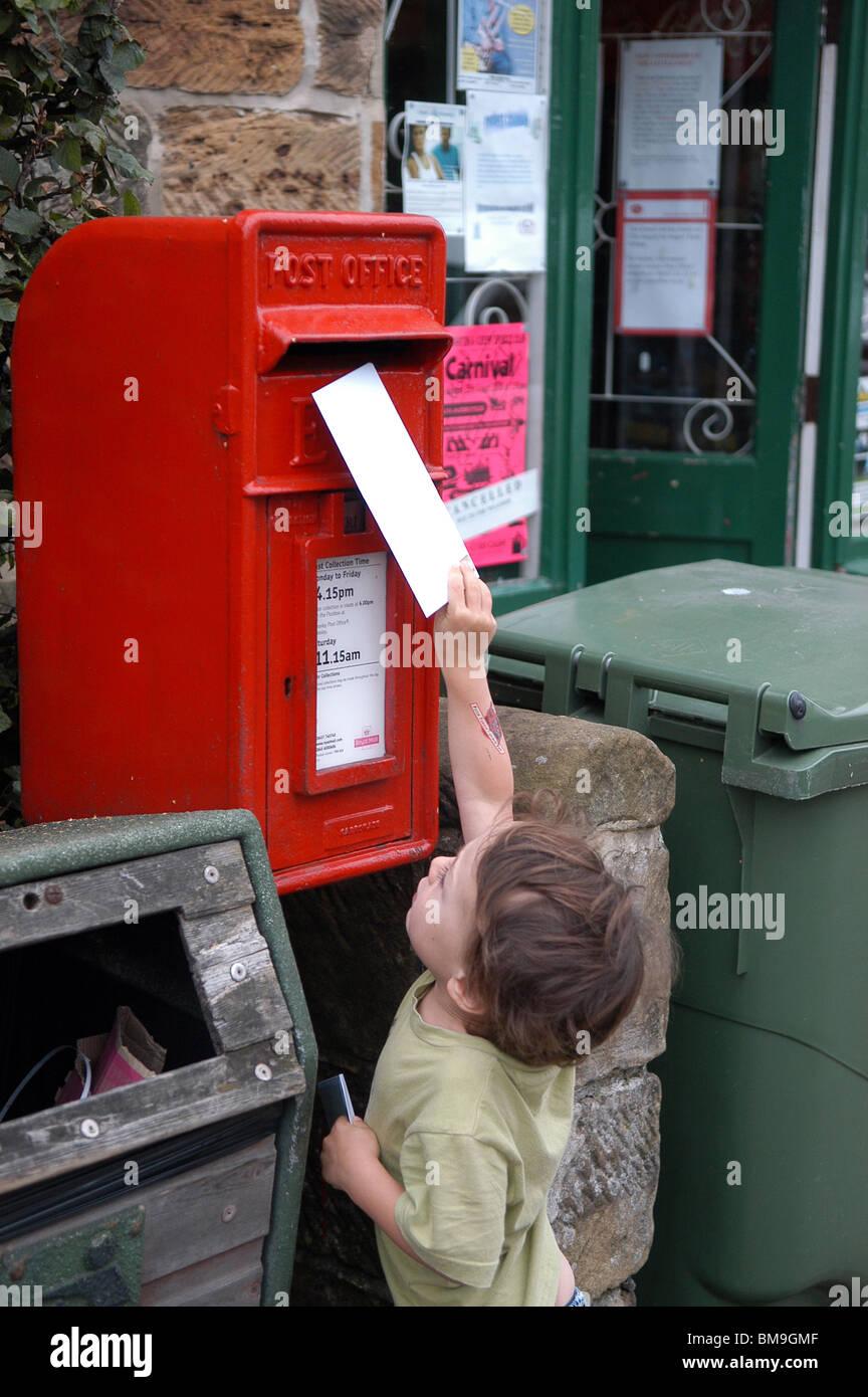 little boy posting a letter - Stock Image