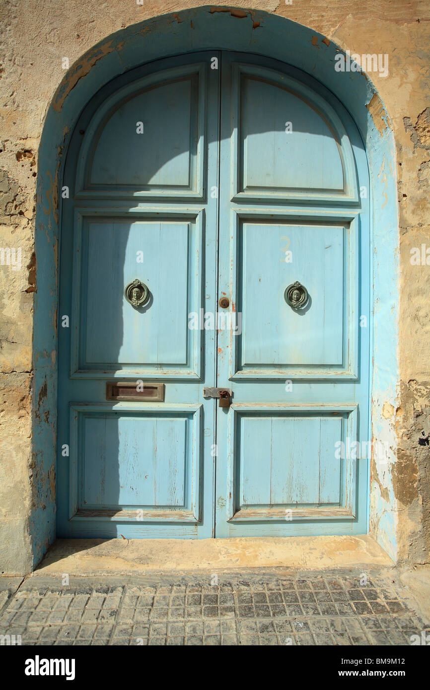 A doorway set into an arch with blue peeling paint, Mdina, Malta - Stock Image