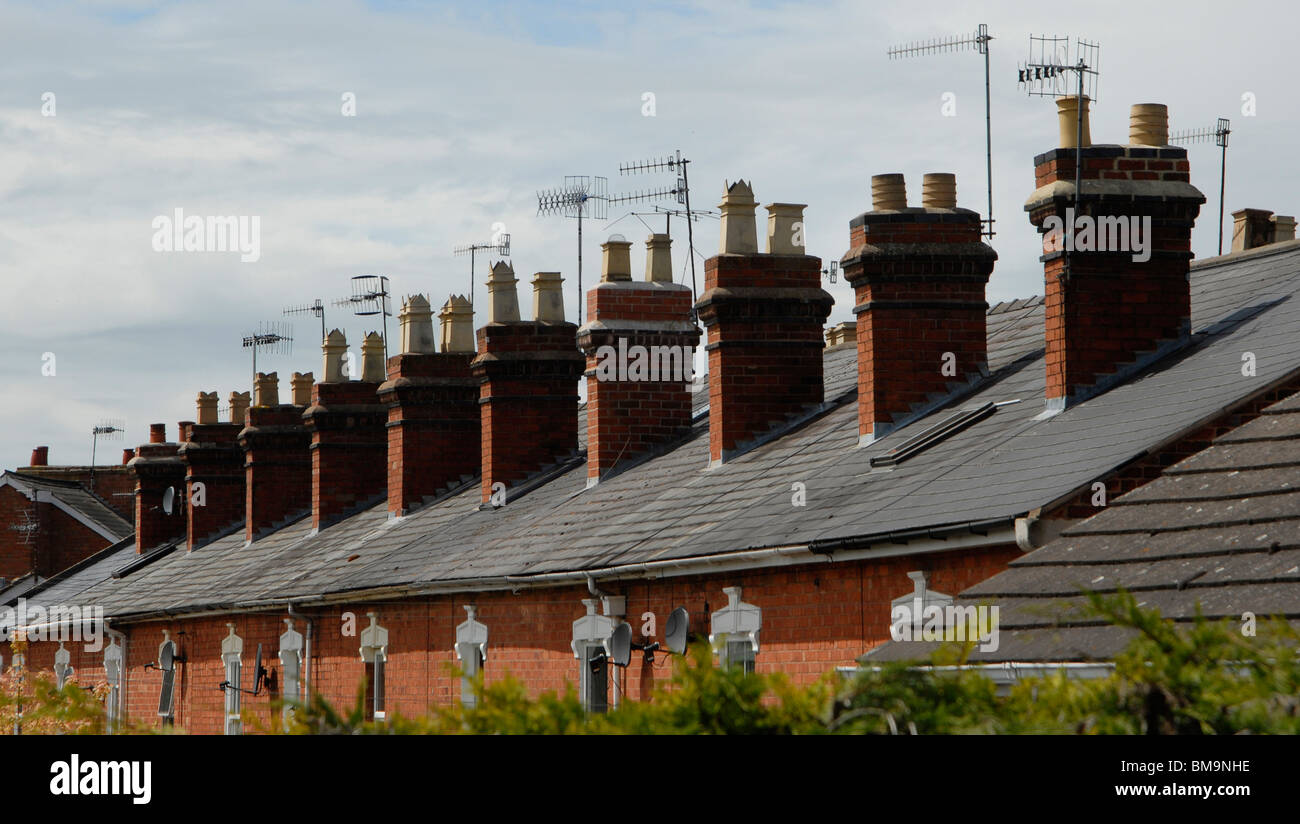 Tv aerials on chimney stacks on a terrace of homes in the city of Worcester. - Stock Image
