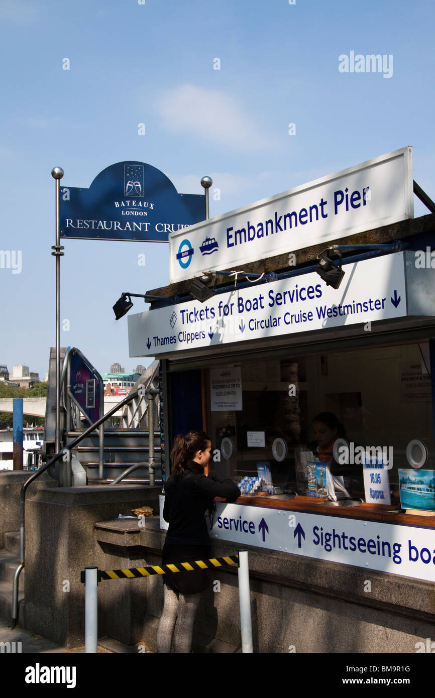A woman buying a ticket for a boat ride, Embankment Pier , London , England - Stock Image