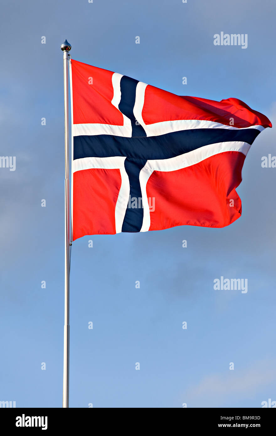 Norwegian Flag Flies Proudly in a Breeze from a Flagpole in a Clear Blue Sky - Stock Image