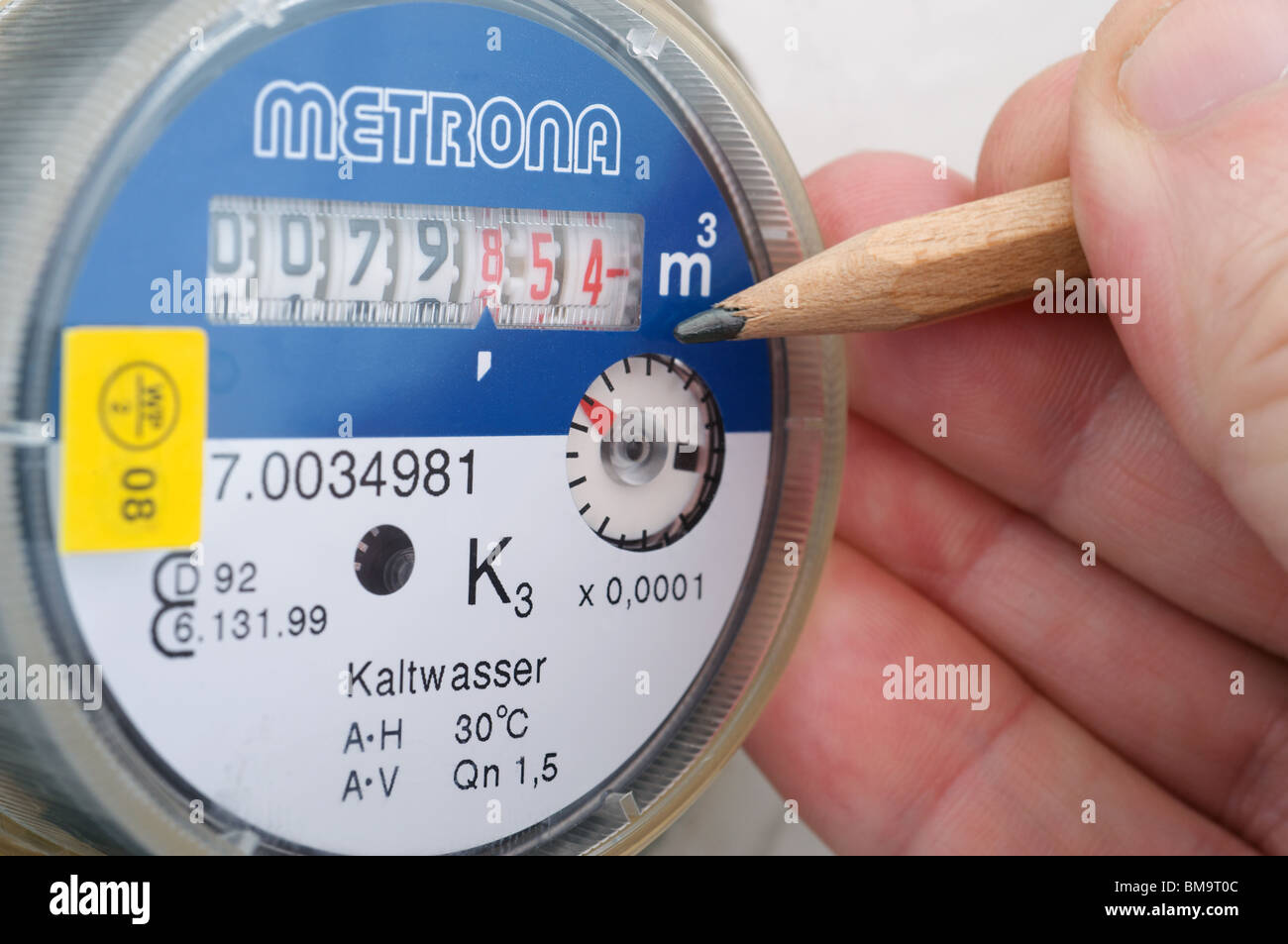 Householder checking the readout on a water meter - Stock Image