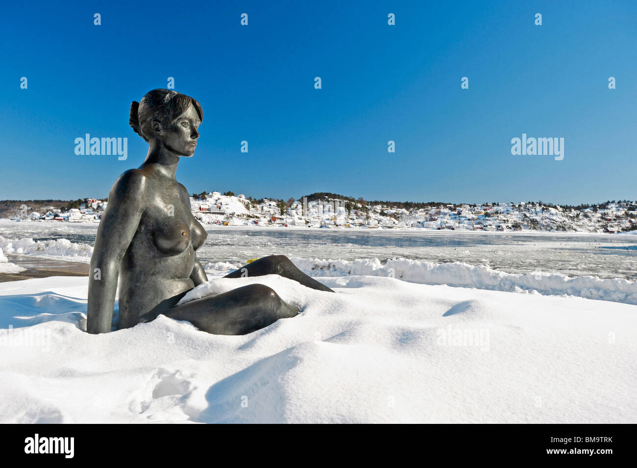 Statue in deep winter snow on the waterfront at Arendal with view across the frozen waters of the harbour - Stock Image