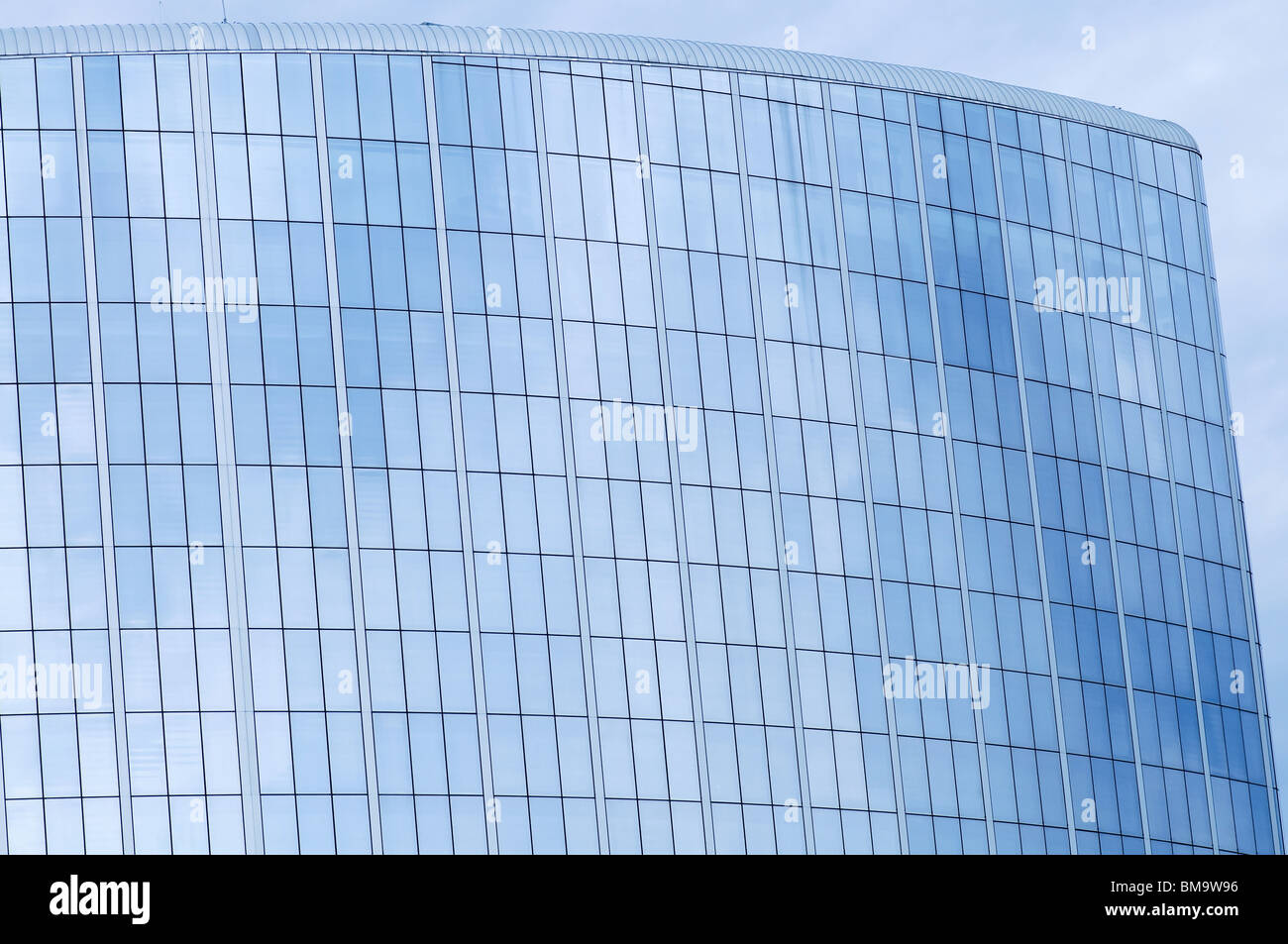 Glass wall of business center and sky reflection - Stock Image