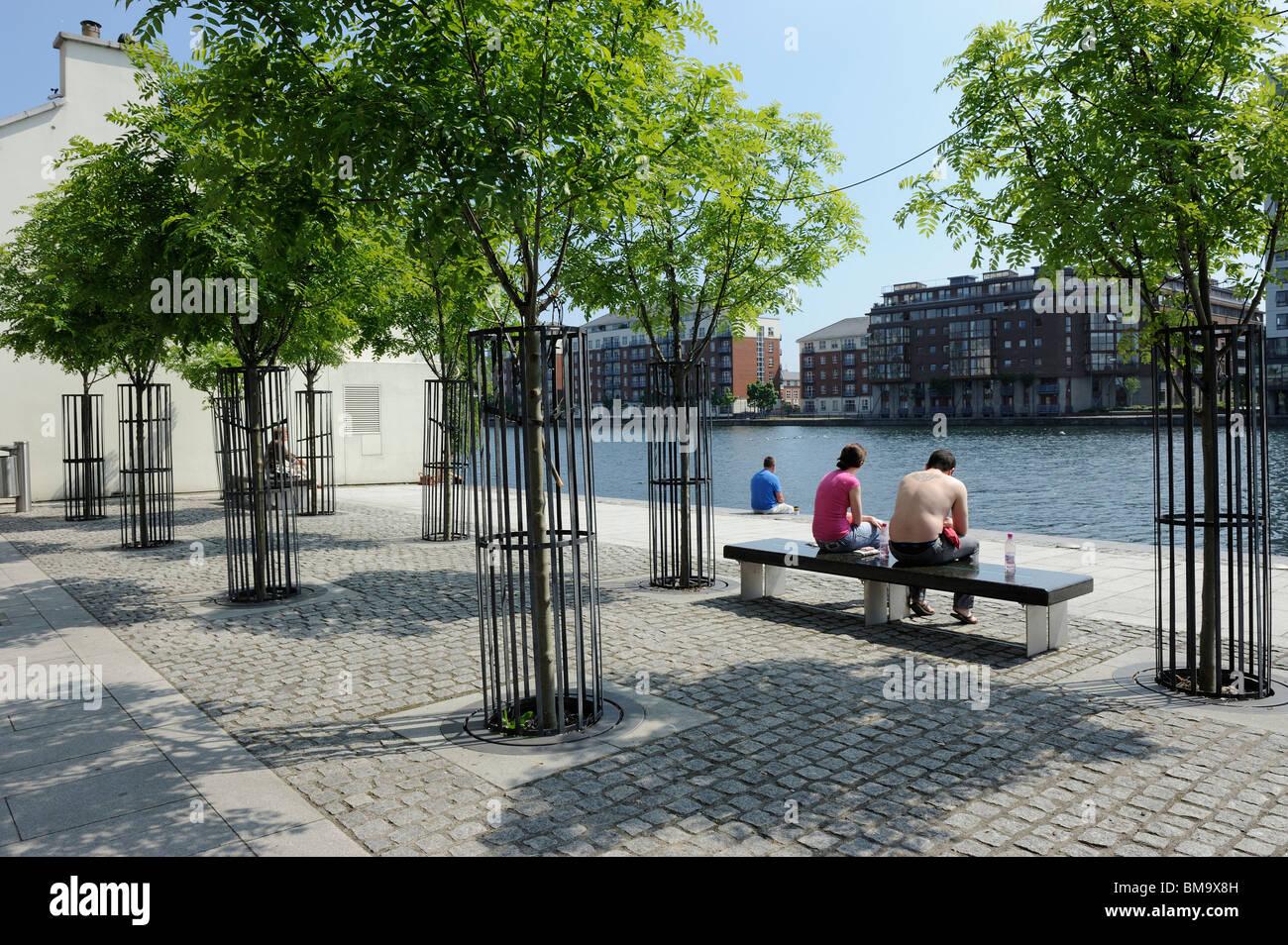 Couple enjoying their leisure time sitting near the river Liffey in Dublin City, Ireland. - Stock Image