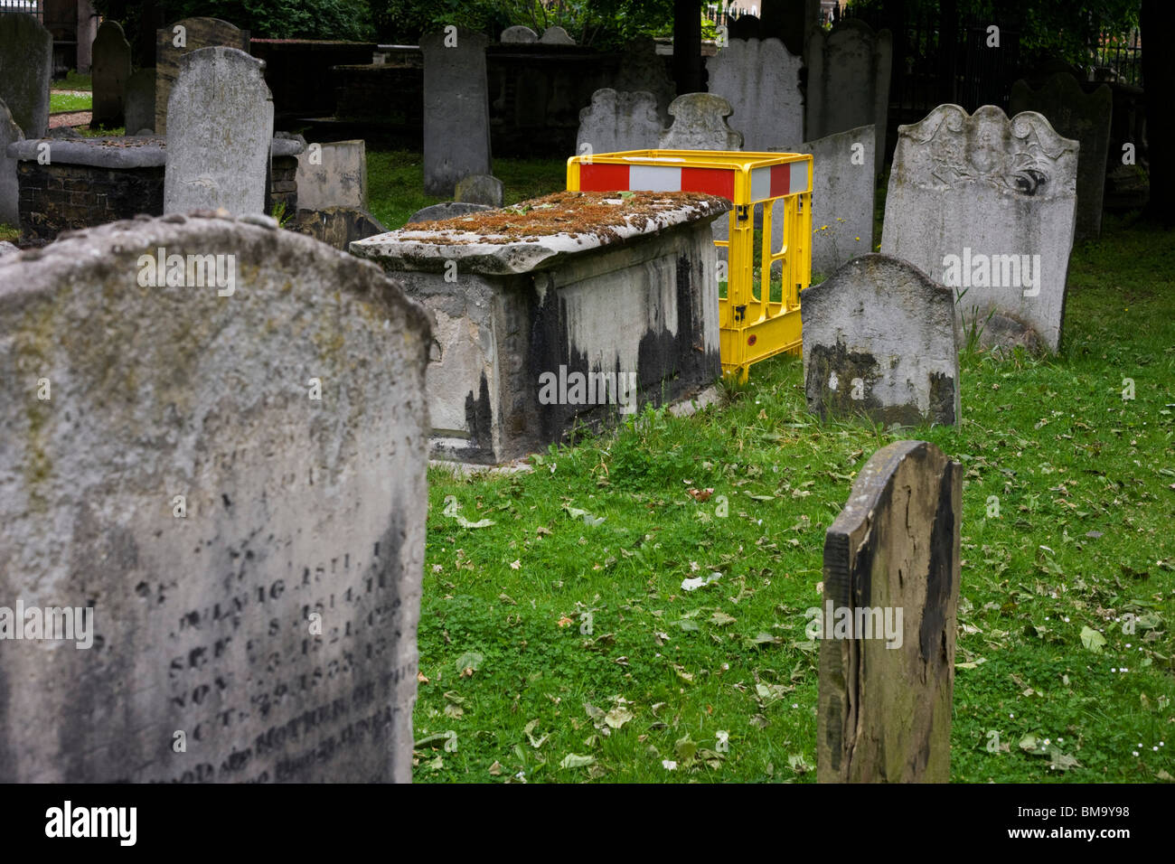 Construction fencing among the historical Victorian headstones of Bunhill Fields cemetery in the City of London. Stock Photo
