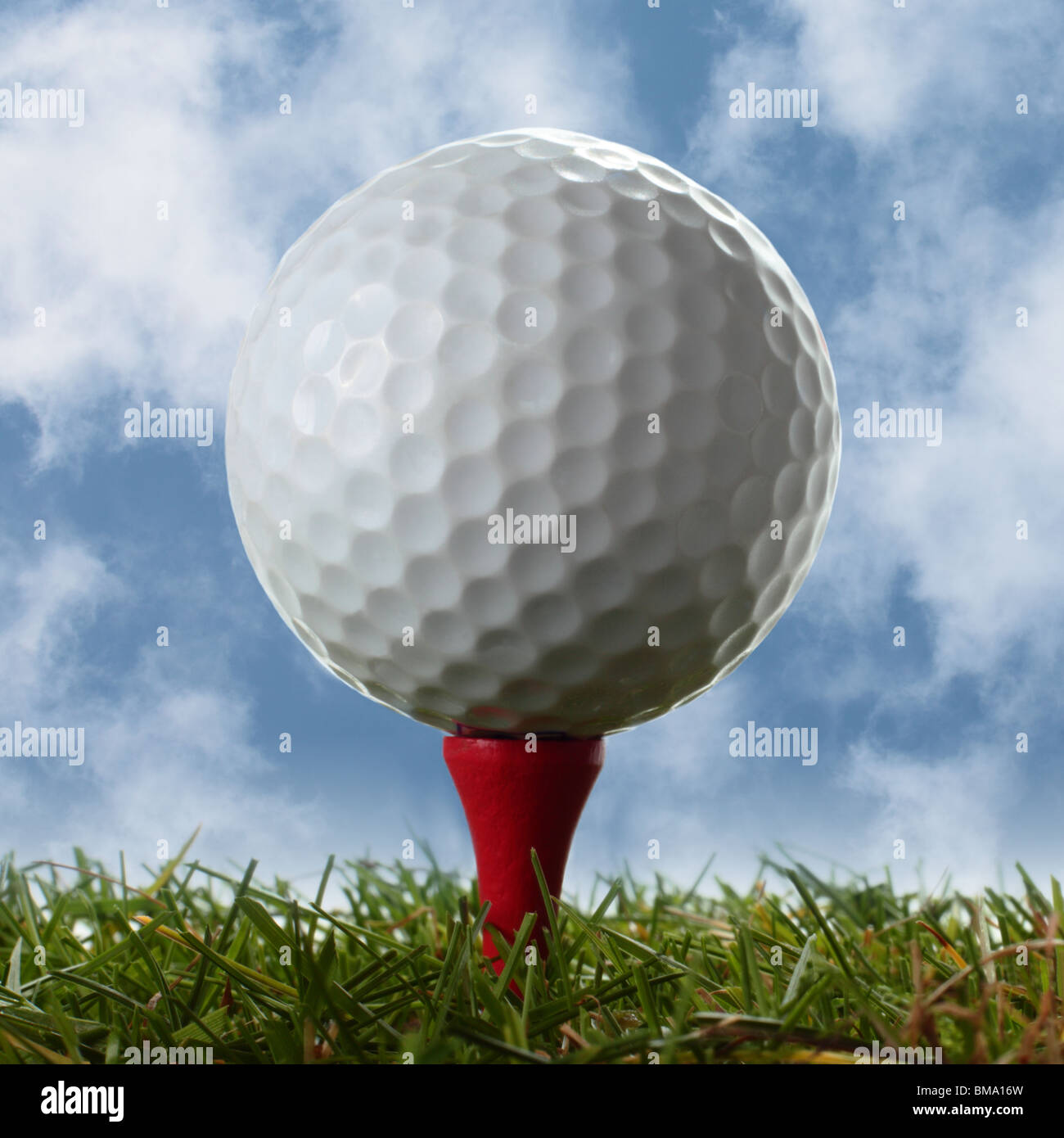 Close Up Of Golf Ball On Red Tee Above Real Grass With Cloudy Blue Stock Photo Alamy