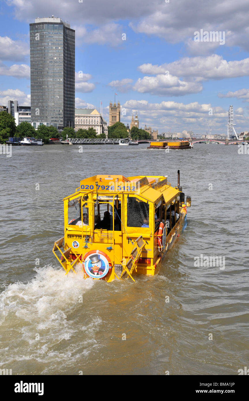 Duck Tours amphibious transport yellow sightseeing tour boat for tourist travel on River Thames towards Millbank - Stock Image