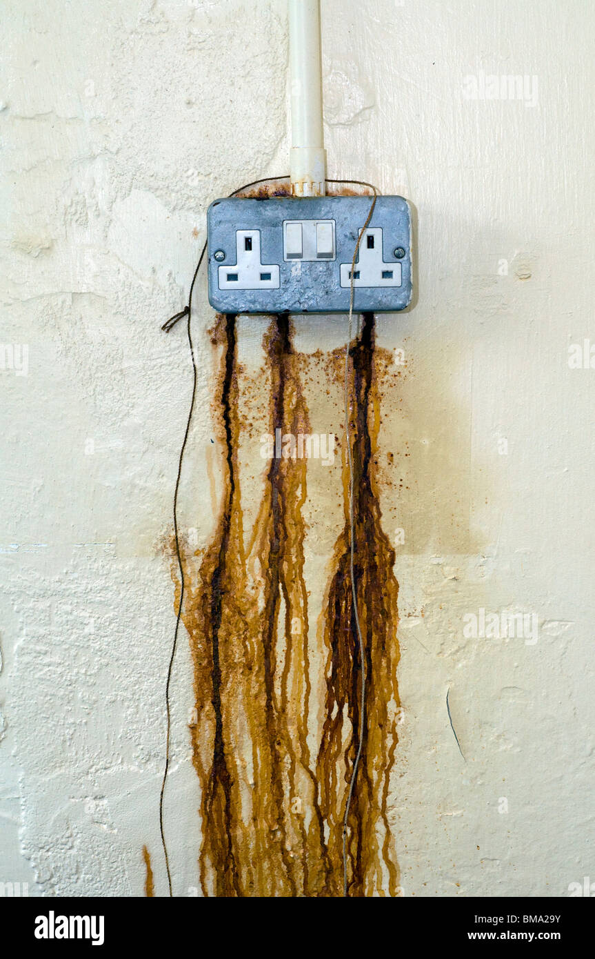 Rust seeping from electrical power point,abstract,electricity prices, health and safety,HSE,IOSH,EOSH,leaking power - Stock Image