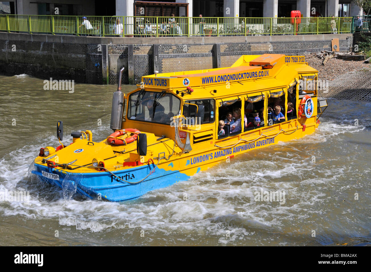 Front & side close up view of people in unusual dual purpose touristy boat splash into Thames for sightseeing - Stock Image