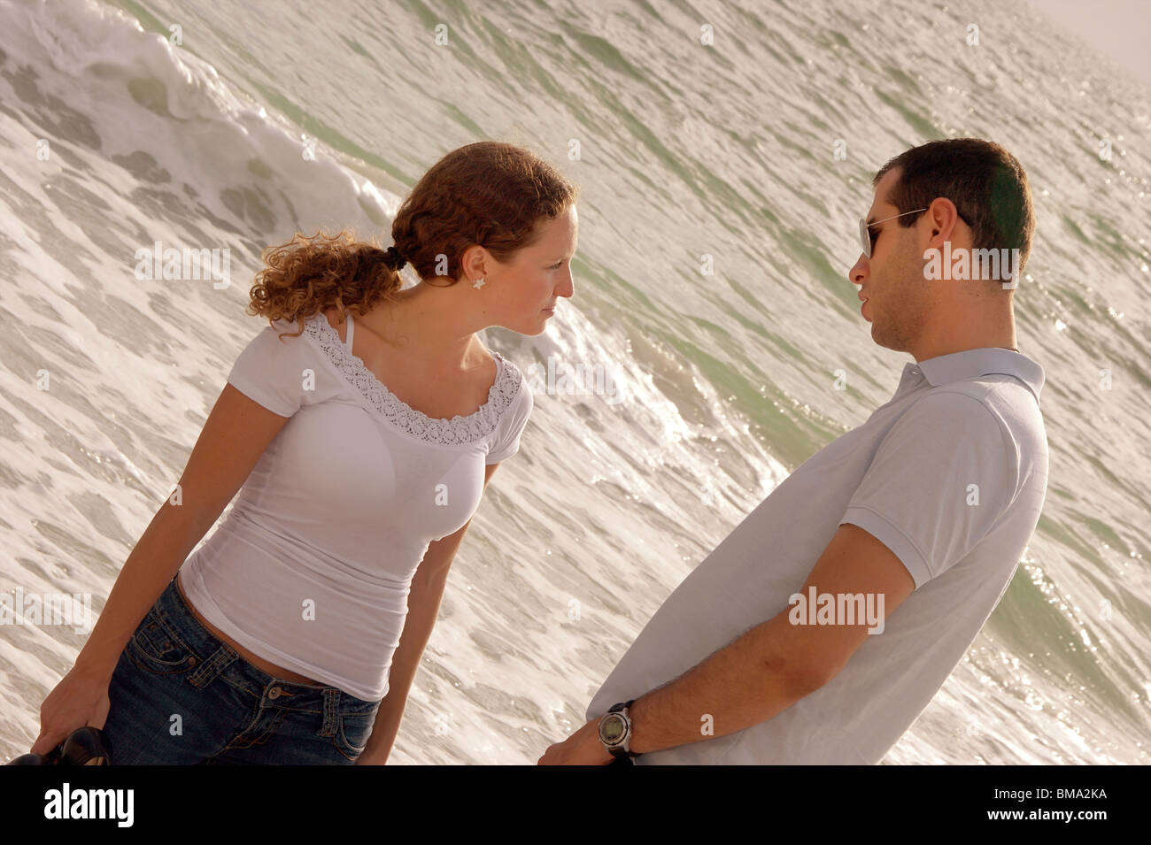 Young Couple At The Beach In The Gulf Of Mexico Having A Serious Talk At The