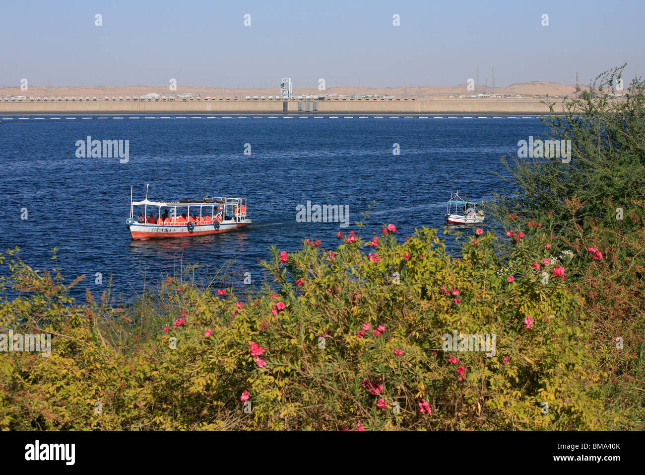 Tourist boat headed for Philae Island with the Old Aswan Dam in the background - Stock Image