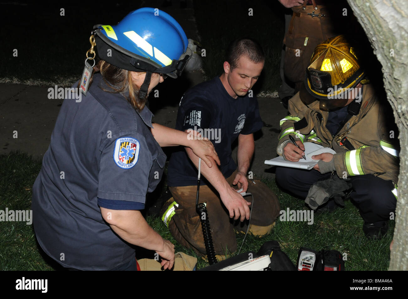 medics check out a firefighter that had been fighting a 3 alarm fire in Greenbelt, Maryland - Stock Image
