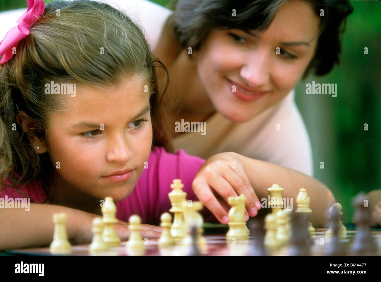 Mom looks on as daughter plays chess. - Stock Image