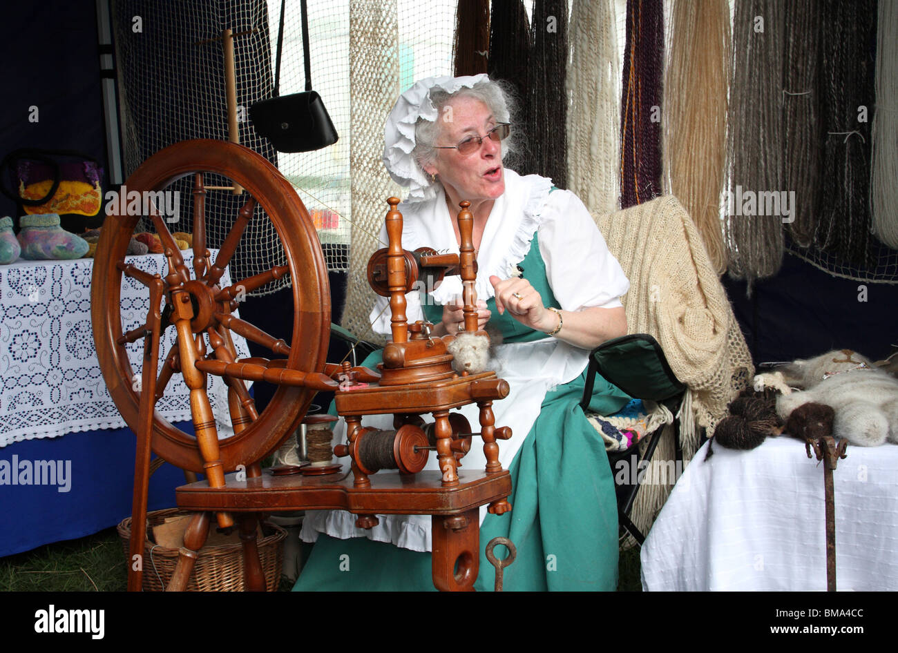 A woman in costume spinning wool at the Chatsworth Show, Derbyshire, England, U.K. - Stock Image