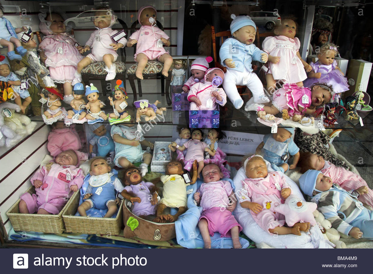 Reborn baby dolls in a shop window display. Skegness, Lincolnshire, UK. - Stock Image
