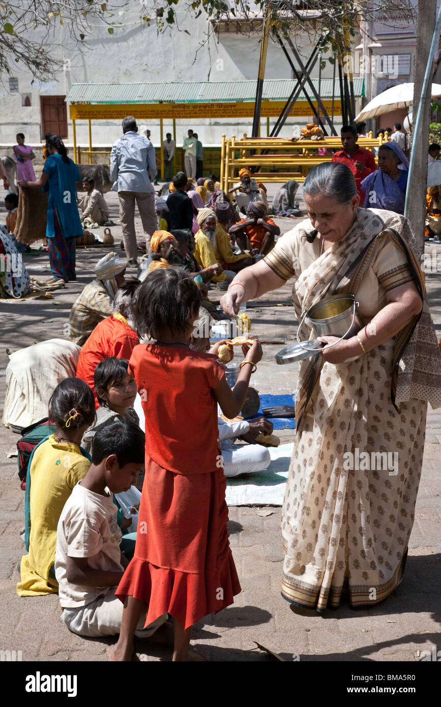 Woman giving food to the beggars. Orchha. India - Stock Image