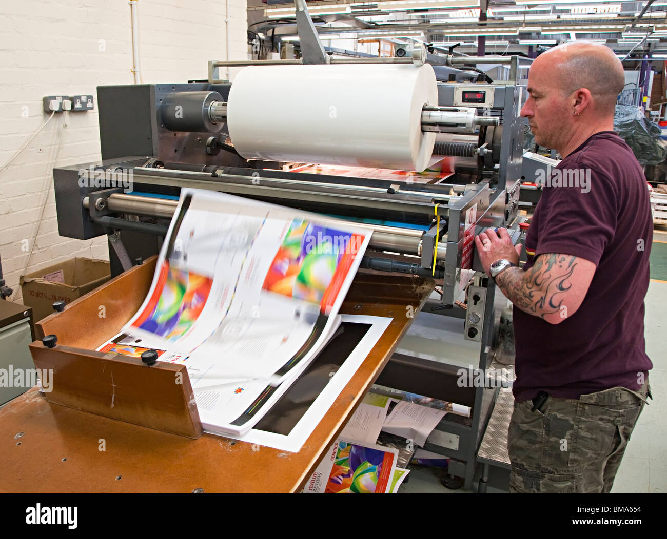 Man working with laminating machine with sheet speeding off roll Wales UK - Stock Image