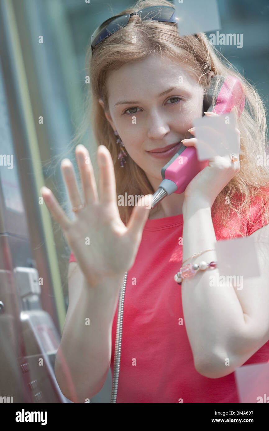 Young casual woman in call box. Focus on face. - Stock Image