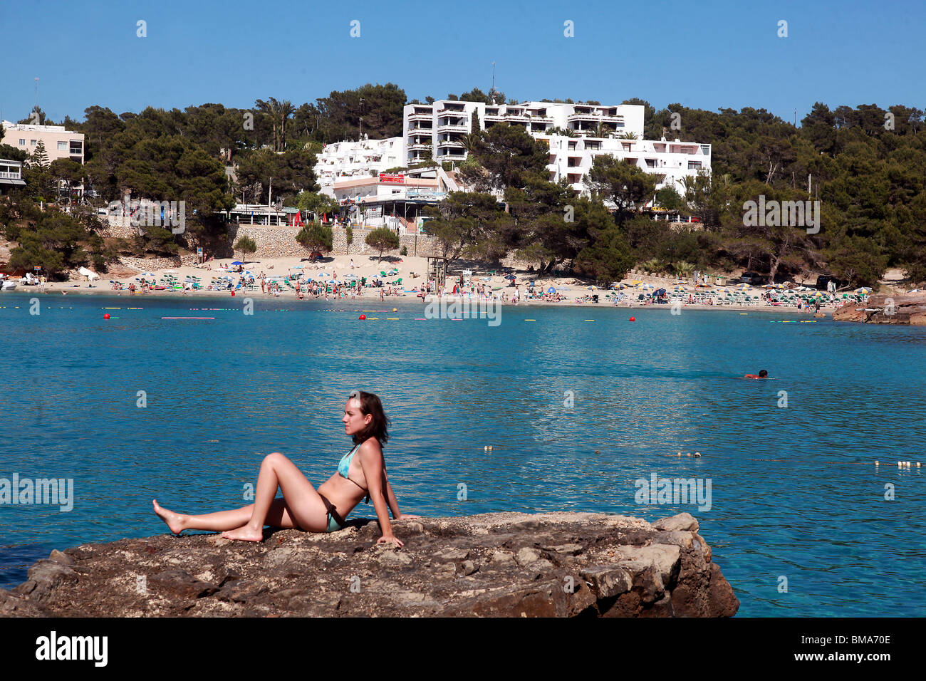 A sunbather enjoys the views of the beach at Portinatx on the island of Ibiza. - Stock Image