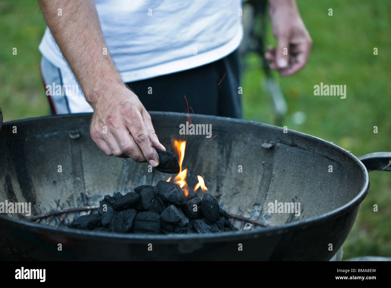 Man holding charcoal briquette and lighting the barbecue grill. & Man holding charcoal briquette and lighting the barbecue grill Stock ...