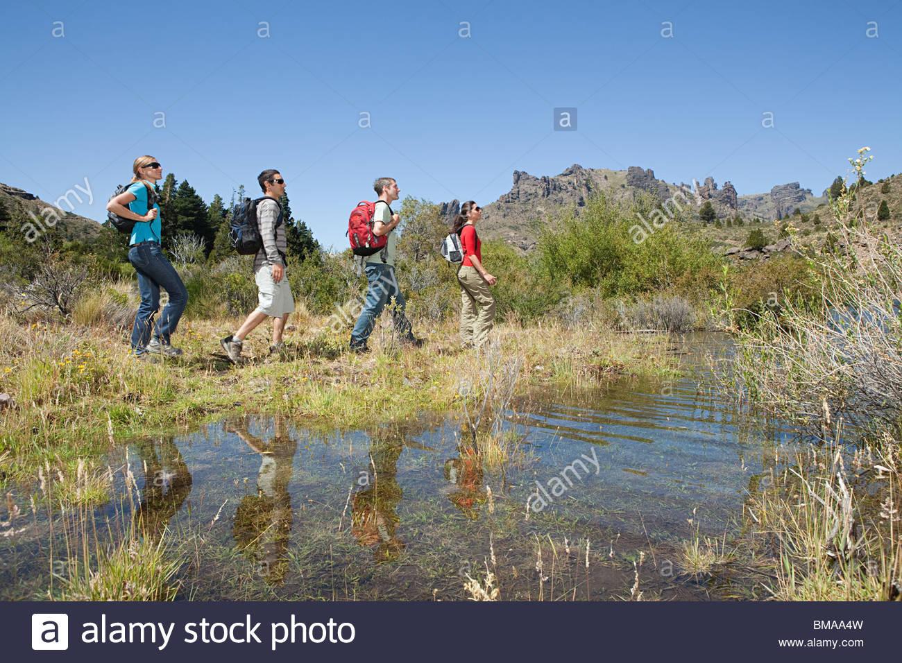 Hikers walking by lake - Stock Image
