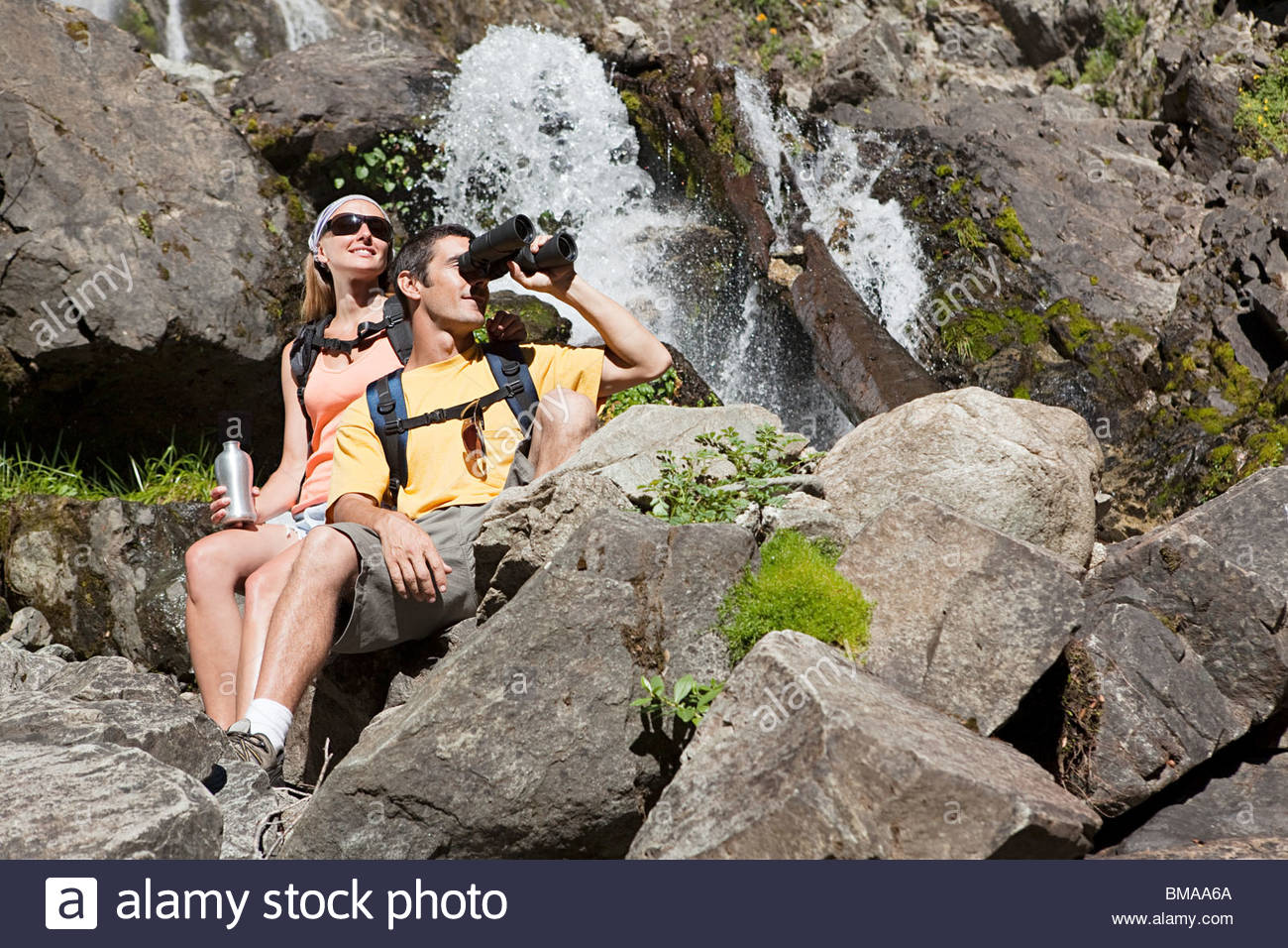 Couple by waterfall with binoculars - Stock Image