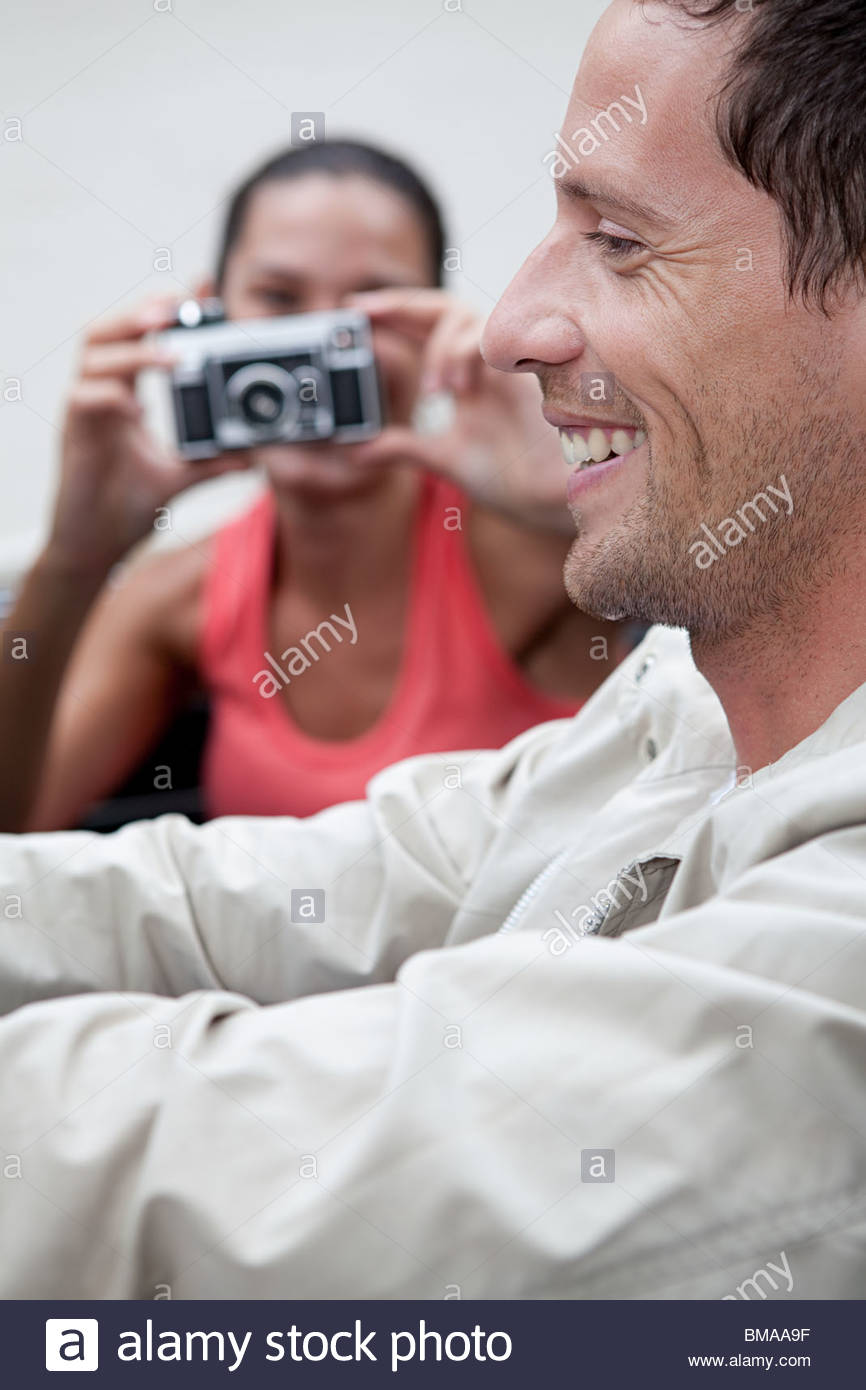 Young woman taking photograph of man in convertible car - Stock Image