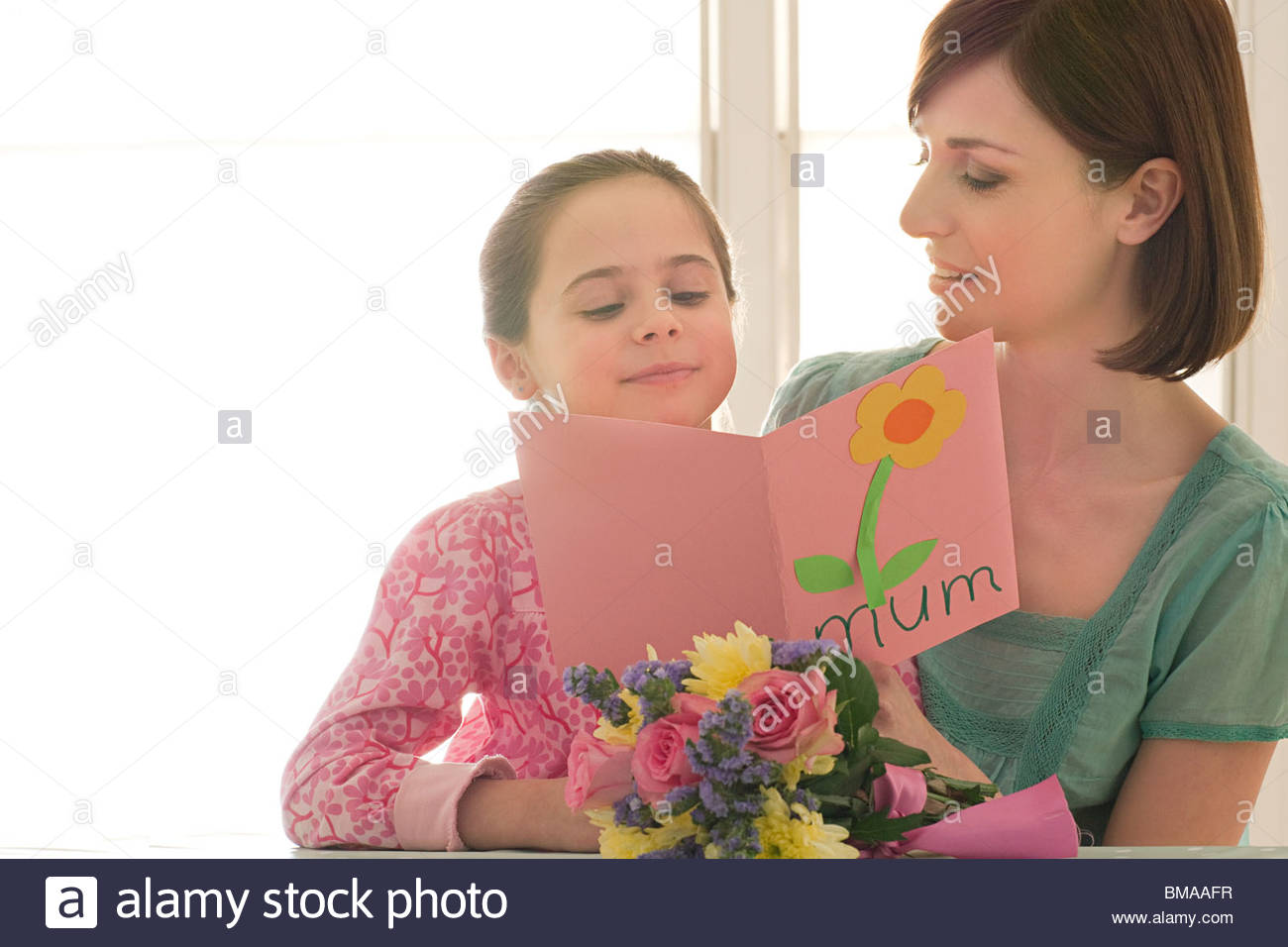 Young girl giving Mothering Sunday card - Stock Image