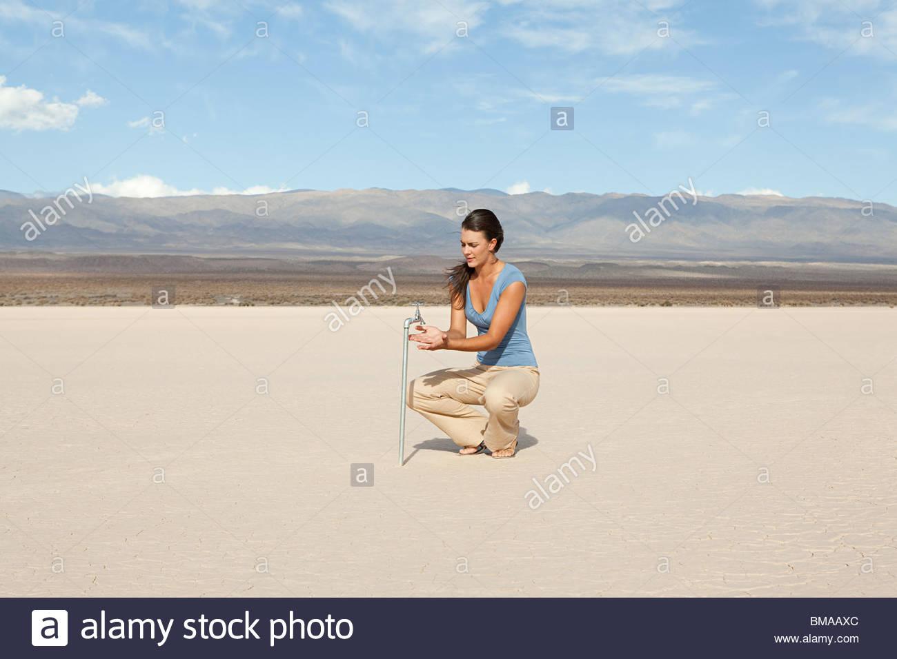 Woman using faucet in desert landscape - Stock Image