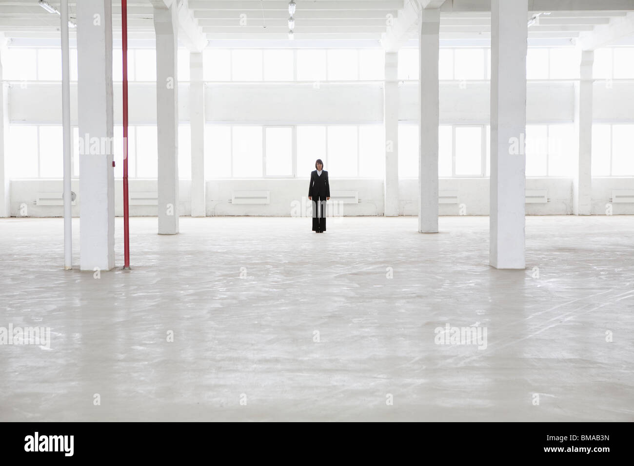 Distant woman stands in empty warehouse - Stock Image