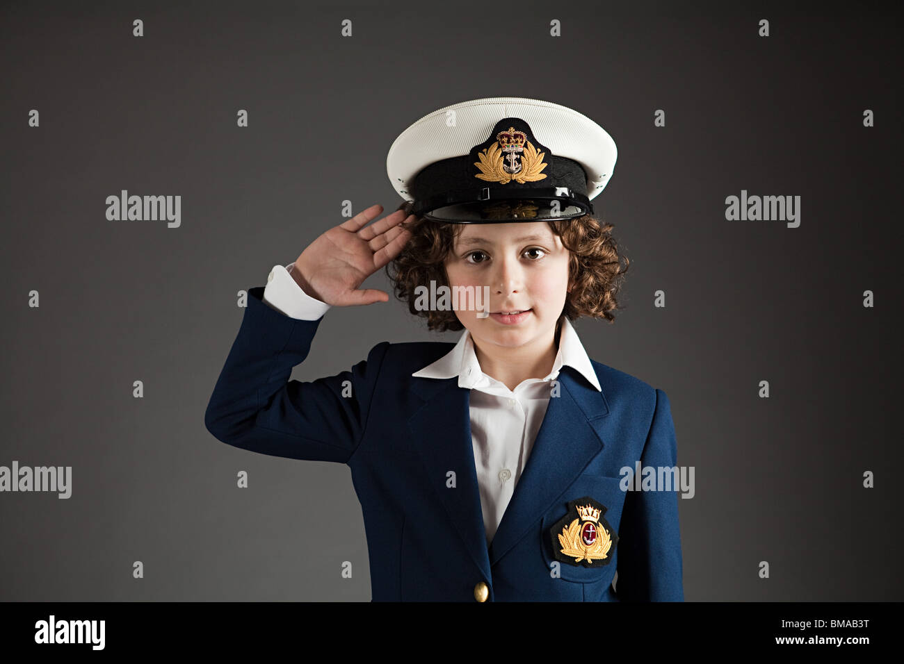 Young boy dressed up in sailor outfit, saluting - Stock Image