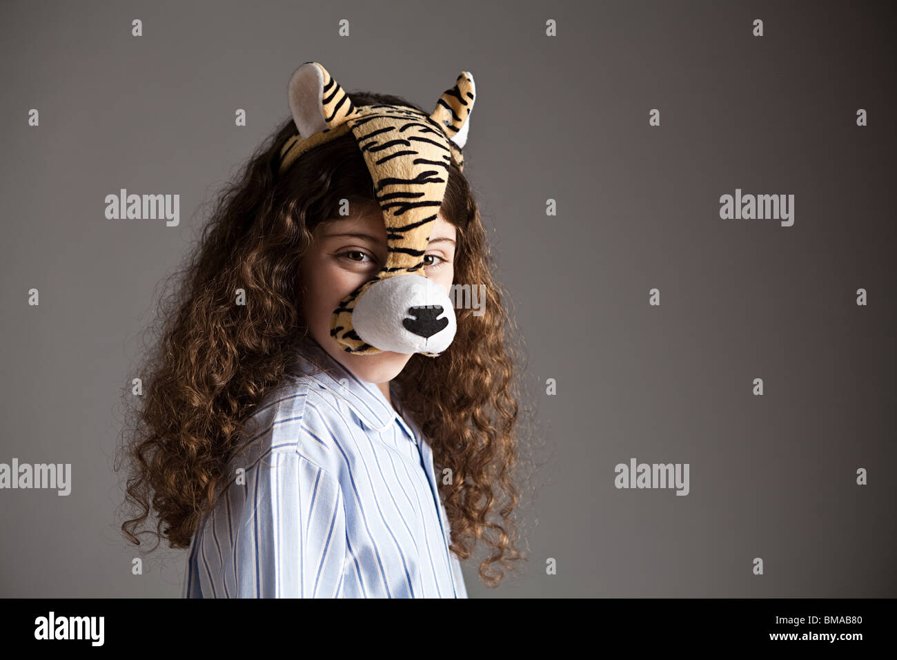 Young girl wearing tiger mask Stock Photo