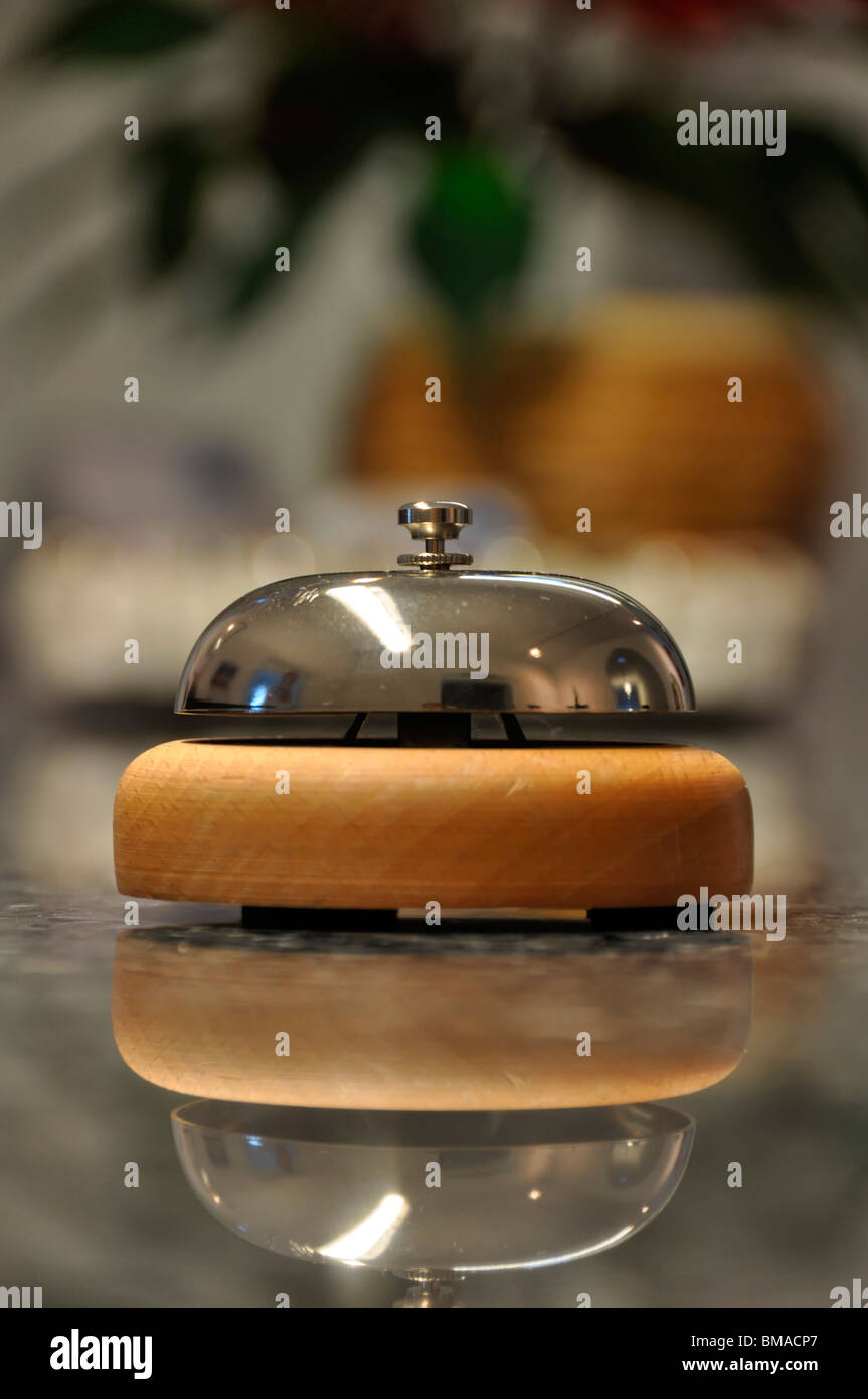 Detail shot of a service bell located on a hotel reception desk with blurred details in the background and reflection - Stock Image