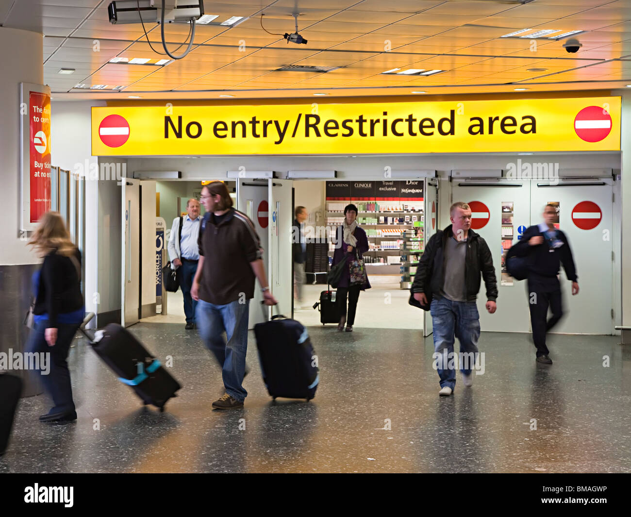 People walking out of restricted customs area international arrivals south terminal Gatwick airport England UK - Stock Image