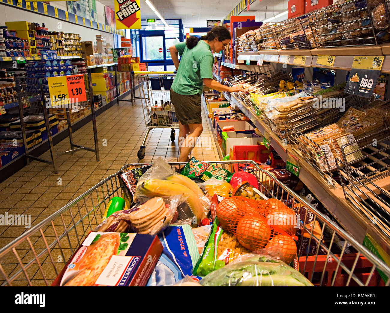 Woman choosing food with shopping trolley in supermarket aisle Wales UK - Stock Image