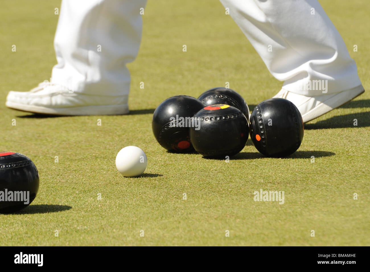 A photograph of lawn bowls with a players feet in the background - Stock Image
