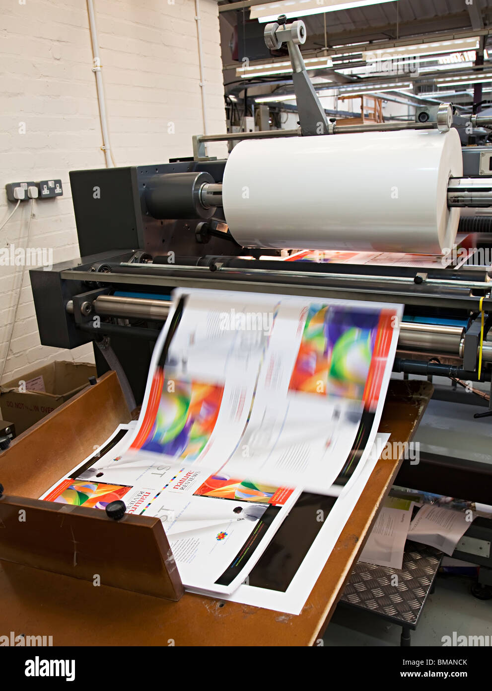 Laminating machine with laminated sheet of paper speeding off roll Wales UK - Stock Image