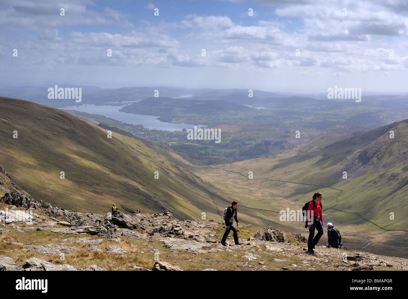 Walkers on Hart Crag in the Lake District with Ambleside and Lake Windermere in the distance - Stock Image