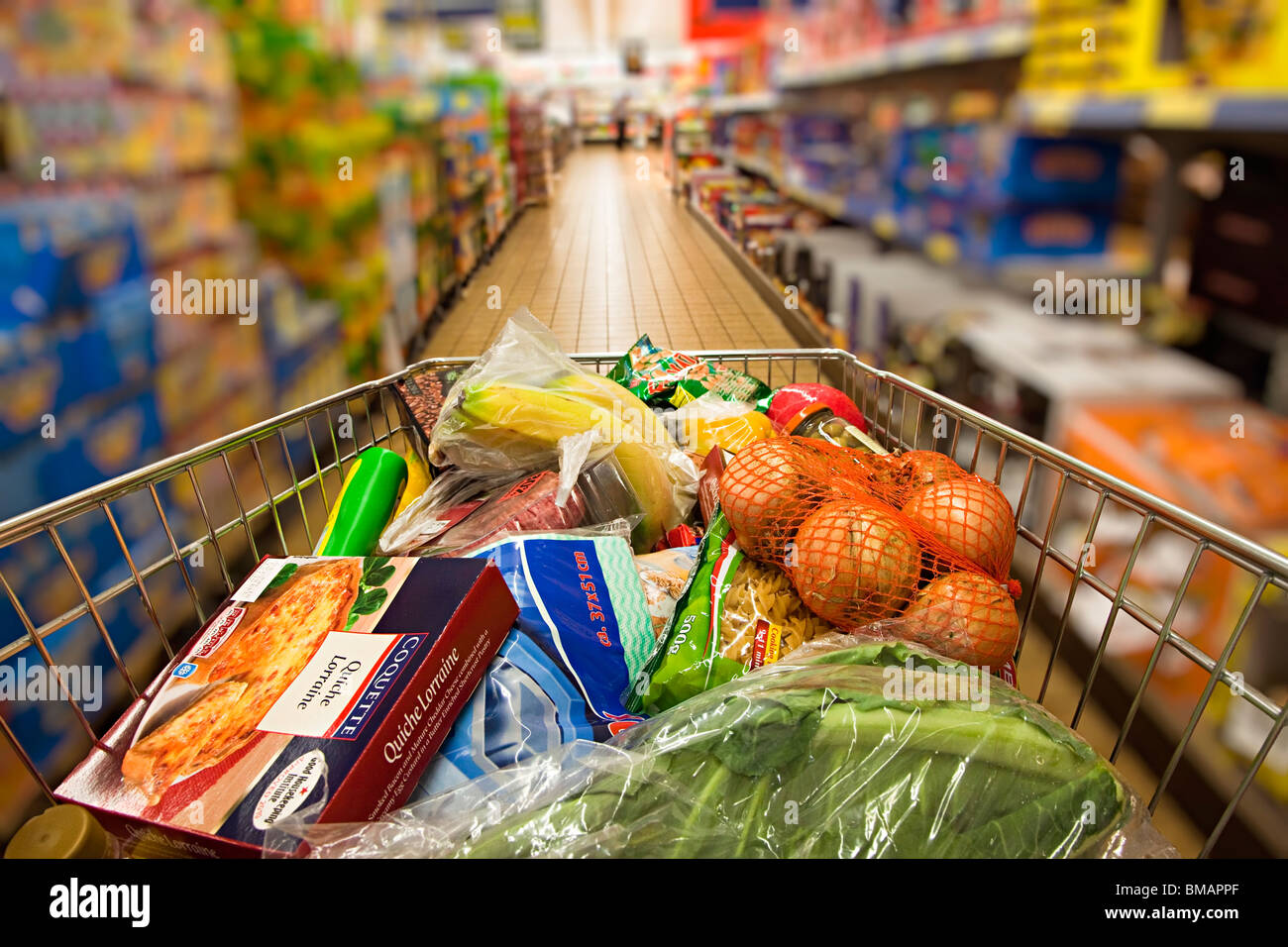 Shopping trolley being pushed down Lidl supermarket aisle Wales UK with person blurred in background - Stock Image