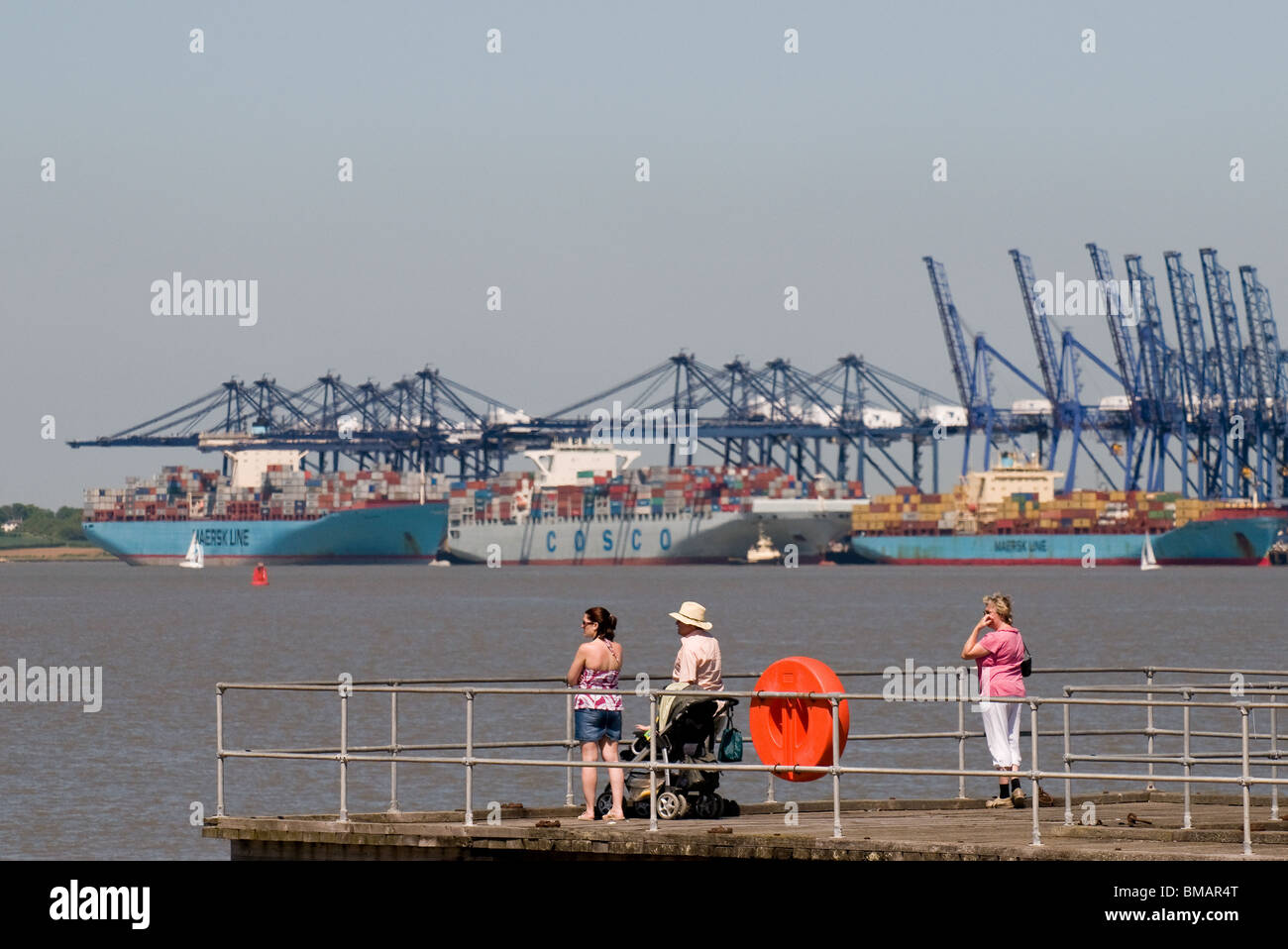 People standing on a jetty near the Port of Felixstowe in Suffolk - Stock Image