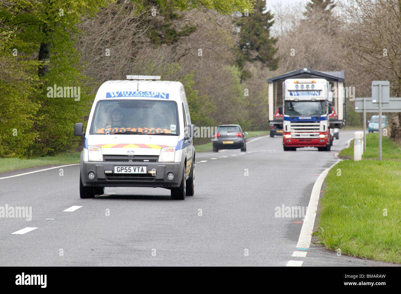 Abnormal load wide load escort vehicle warning on coming traffic with articulated lorry carrying a wide load behind - Stock Image
