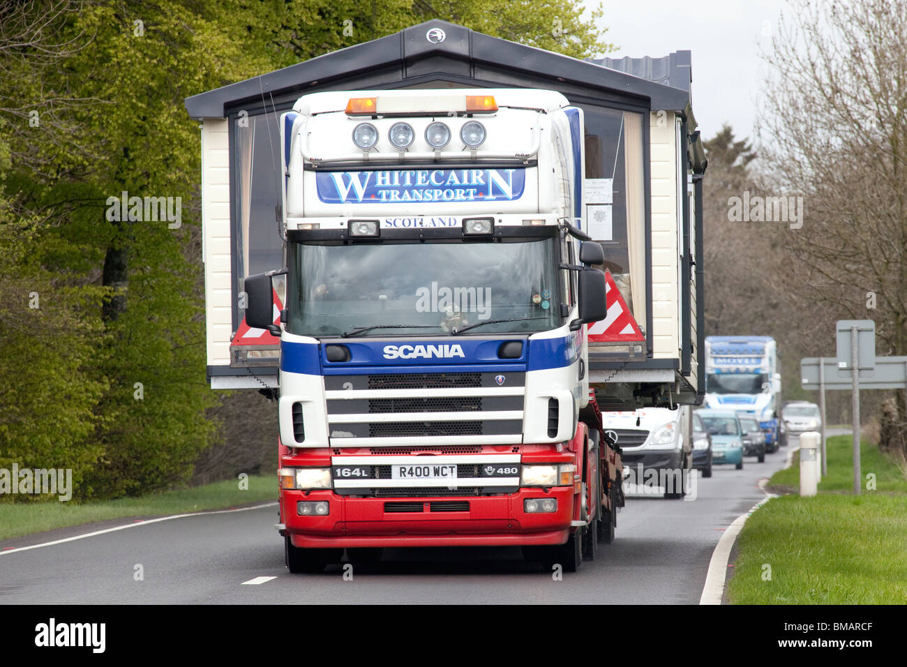 A wide or abnormal load on the back of a lorry traveling along road A75 with queue of traffic behind UK - Stock Image
