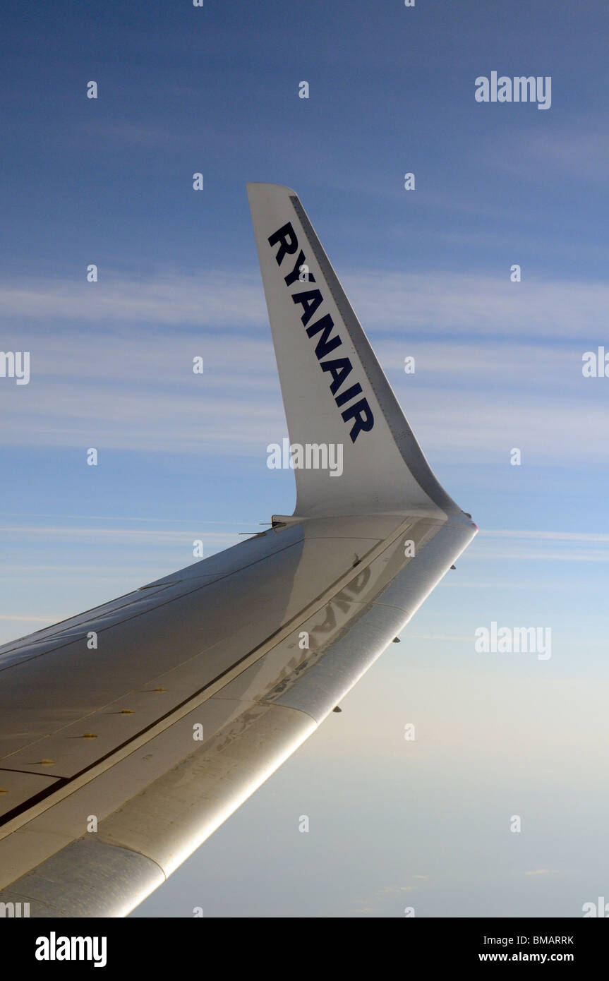Aircraft winglet carrying the name Ryanair a low cost European airline and open skies backdrop seen from the cabin - Stock Image