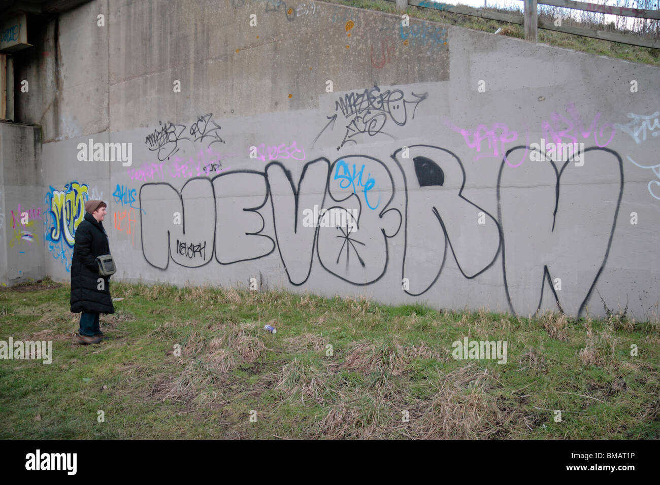 A woman looks at graffiti scrawled on a concrete wall in brentford middx uk